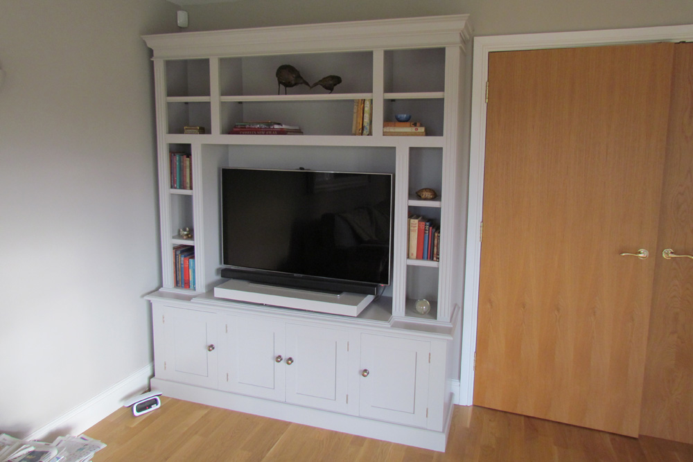 Painted open top wall unit to house TV with a pull out shelve and swivel mechanism with 4 shaker style doors below Finished with fluted pillars